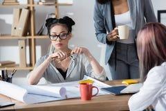 Азиатская коммерсантка в eyeglasses сидя на таблице с коллегами и работая в офисе Стоковое фото RF