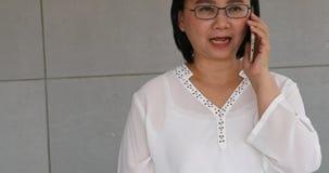 Азиатская коммерсантка говоря с мобильным телефоном сток-видео