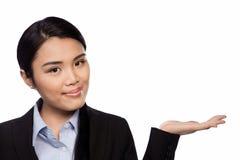Азиатская коммерсантка держа вне ее ладонь Стоковые Изображения RF