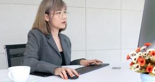 Азиатская коммерсантка используя компьютер в офисе сток-видео