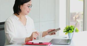Азиатская коммерсантка используя ноутбук в офисе видеоматериал