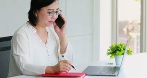 Азиатская коммерсантка используя ноутбук в офисе сток-видео