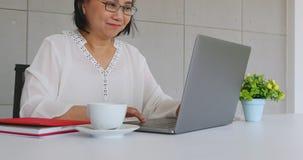 Азиатская коммерсантка используя ноутбук в офисе акции видеоматериалы