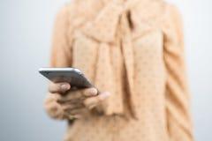 Азиатская коммерсантка используя умный телефон на серой предпосылке Стоковая Фотография RF