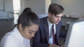 Азиатская коммерсантка и бизнесмен работая на компьютерах, обсуждая проект в офисе 4K акции видеоматериалы
