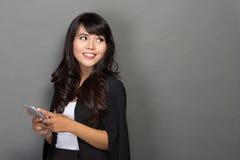 Азиатская коммерсантка при ее телефон смотря вверх Стоковая Фотография RF