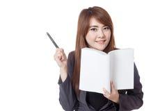 Азиатская коммерсантка прочитала книгу и указывает ручка к ее праву стоковая фотография