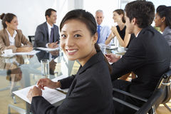 Азиатская коммерсантка сидя вокруг таблицы зала заседаний правления с коллегами стоковое фото