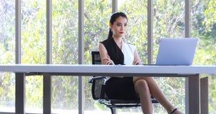 Азиатская коммерсантка смотря ноутбук в офисе сток-видео