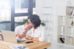 Азиатская коммерсантка с дочерью в офисе Стоковые Фото
