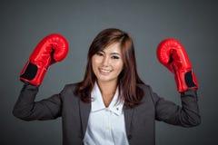Азиатская коммерсантка с перчаткой бокса показывает ей кулаки Стоковые Фотографии RF