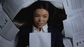 Азиатская коммерсантка читая успешный контракт, счастливый для того чтобы закончить работу, overhours сток-видео