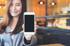 Азиатская красивая бизнес-леди держа и показывая белый мобильный телефон с пустой черной стороной экрана и smiley в кафе Стоковое фото RF