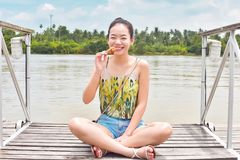 Азиатская красивая женщина принимает остатки около реки стоковая фотография rf