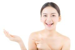 Азиатская красивая молодая женщина показывая при здоровая чистая кожа представляя что-то Стоковое фото RF