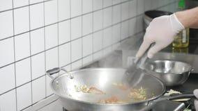 Азиатская кухня ресторана, шеф-повар варя еду, молодой человек как профессиональная деятельность кашевара сток-видео