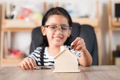 Азиатская маленькая девочка в класть монетку внутри для того чтобы расквартировать копилку отмелую Стоковая Фотография RF