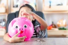 Азиатская маленькая девочка в класть монетку внутри к малой глубине копилки Стоковое фото RF