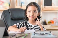 Азиатская маленькая девочка делая домашнюю работу на фокусе деревянного стола отборном sh Стоковые Изображения