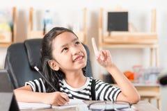 Азиатская маленькая девочка делая домашнюю работу на фокусе деревянного стола отборном sh Стоковые Изображения RF