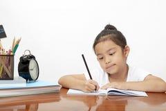 Азиатская маленькая девочка делая ее домашнюю работу стоковые изображения rf