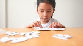 Азиатская маленькая девочка играя малую глубину фокуса мозаики отборную в наличии поля видеоматериал