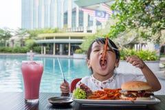Азиатская маленькая китайская девушка есть фраи бургера и француза Стоковые Изображения RF
