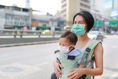 Азиатская мама нося ее младенца hipseat идя с носить маску защиты против загрязнения воздуха в городе Бангкока r стоковая фотография rf