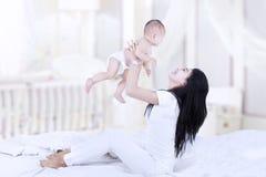 Азиатская мама поднимая младенца Стоковые Фотографии RF