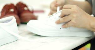 Азиатская мать делая шнурок для ваших ботинок ребенка сток-видео