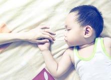 Азиатская мать держа руку младенца пока спящ Стоковая Фотография RF