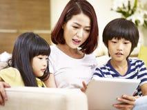 Азиатская мать и 2 дет используя цифровую таблетку совместно Стоковое Изображение RF