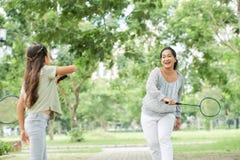 Азиатская мать и дочь играя бадминтон стоковое фото