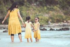 Азиатская мать и дочь идя и играя на пляже Стоковое Изображение RF