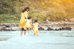 Азиатская мать и дочь идя и играя на пляже Стоковое Изображение