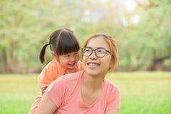 Азиатская мать и ее дочь усмехаясь совместно Стоковые Изображения RF