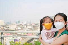Азиатская мать нося ее дочь с носить маску защиты против премьер-министра 2 загрязнение воздуха 5 в городе Бангкока r стоковые изображения rf