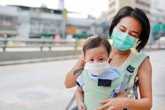 Азиатская мать нося ее младенческого младенца hipseat на открытом воздухе с носить маску защиты против премьер-министра 2 загрязн стоковые изображения