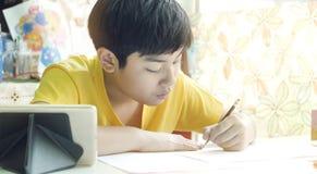 Азиатская мать помогая ее сыну делая домашнюю работу на белой таблице стоковая фотография rf