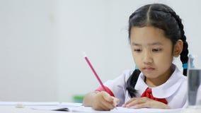 Азиатская маленькая девочка в конце работы тайского студента детского сада равномерном делая домашнем вверх по съемке видеоматериал