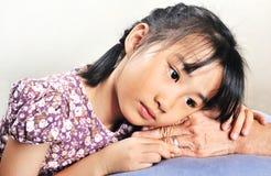 Азиатская маленькая девочка полагаясь ее голова на старшей руке или ее grandmo Стоковые Фотографии RF