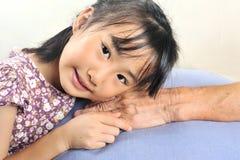 Азиатская маленькая девочка полагаясь ее голова на старшей руке или ее grandmo Стоковые Фото