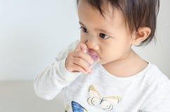 Азиатская маленькая девочка принимает сироп медицины сама стоковые фотографии rf