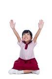 Азиатская маленькая китайская девушка в школьной форме сидя на поле Стоковое фото RF