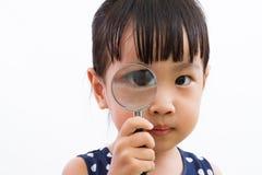 Азиатская маленькая китайская девушка держа лупу Стоковое Изображение