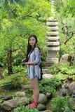 Азиатская модель женщины стоит близко скульптура в лесе Стоковые Фотографии RF