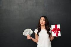 Азиатская молодая думая женщина держа деньги и подарочную коробку Стоковые Изображения