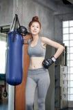 Азиатская молодая женщина боксера фитнеса в перчатках бокса представляя с каламбуром Стоковые Фотографии RF