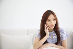 Азиатская молодая женщина вызывая говорить на callephohe телефона в coffeeshop стоковая фотография