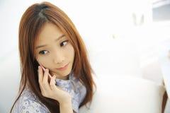 Азиатская молодая женщина вызывая говорить на callephohe телефона в coffeeshop стоковые фото